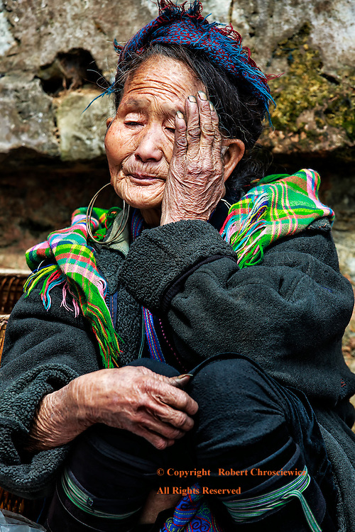 Resting Black Hmong: An elderly woman of the a local hill tribe, the Black Hmong, rests for a moment from a futile attempt to sell her craft work, Sapa Vietnam.
