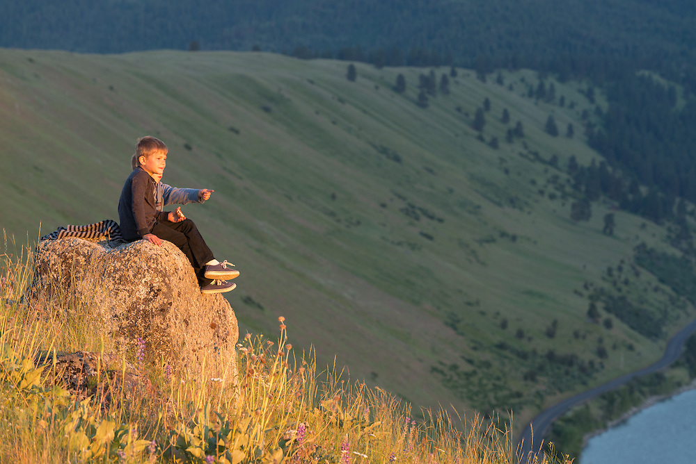 Boys sitting on a boulder on the Wallowa Lake moraine in Oregon's Wallowa Valley.