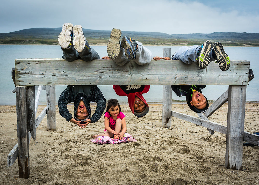 Kids here in Inukjuak can play with almost anything. They are near the beach and it's probably around 10 C only outside.