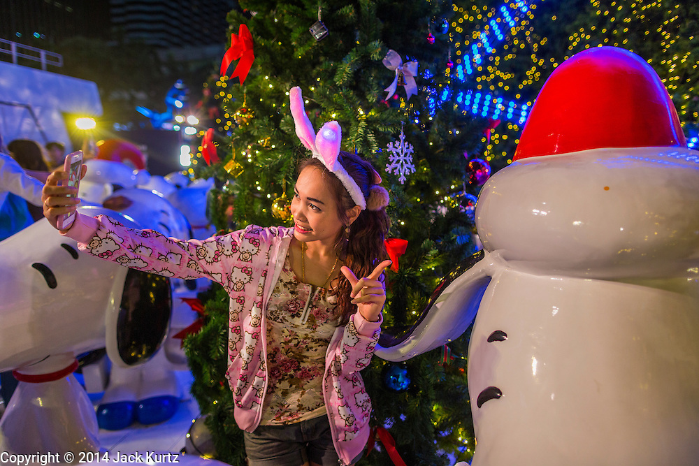 "17 DECEMBER 2014 - BANGKOK, THAILAND: A woman takes a ""selfie"" in front of a  Christmas tree at Central World in Bangkok. Thailand is overwhelmingly Buddhist. Christmas is not a legal holiday in Thailand, but Christmas has become an important commercial holiday in Thailand, especially in Bangkok and communities with a large expatriate population.    PHOTO BY JACK KURTZ"
