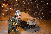 A boy plays snowballs at night during heavy snow showers in central London - a rare event for an inner-city. Snowflakes are falling in large amounts settling on this street in Herne Hill, South London. The lad is in his element by going outdoors at night as the showers are falling everywhere about him. He dashes across the picture, running through thousands of snowflakes armed with a snowball destined for his elder sister's head. Relishing the hide and seek game they're playing and the prospect of landing the snow as a direct hit makes him look mischievous and excited.
