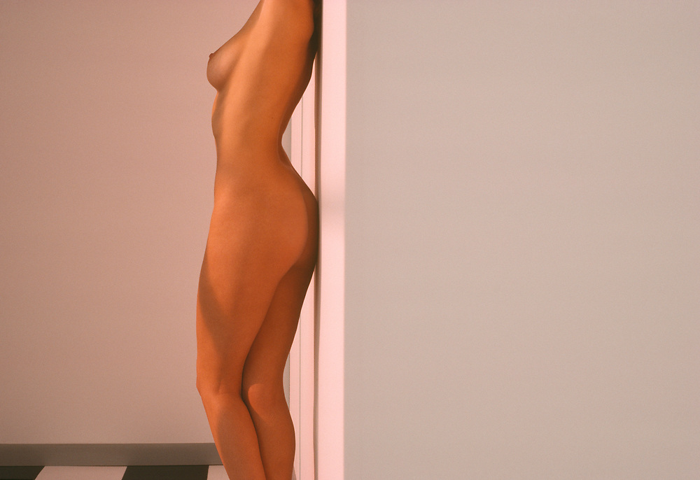 Nude woman leaning against wall being lit with sunlight coming in through window