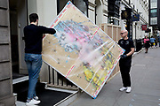 Art removal specialist workmen carry an artwork by Italian artist Marco Grassi, into the Hofer Gallery in Maddox Street, on 30th April 2019, in London, England.