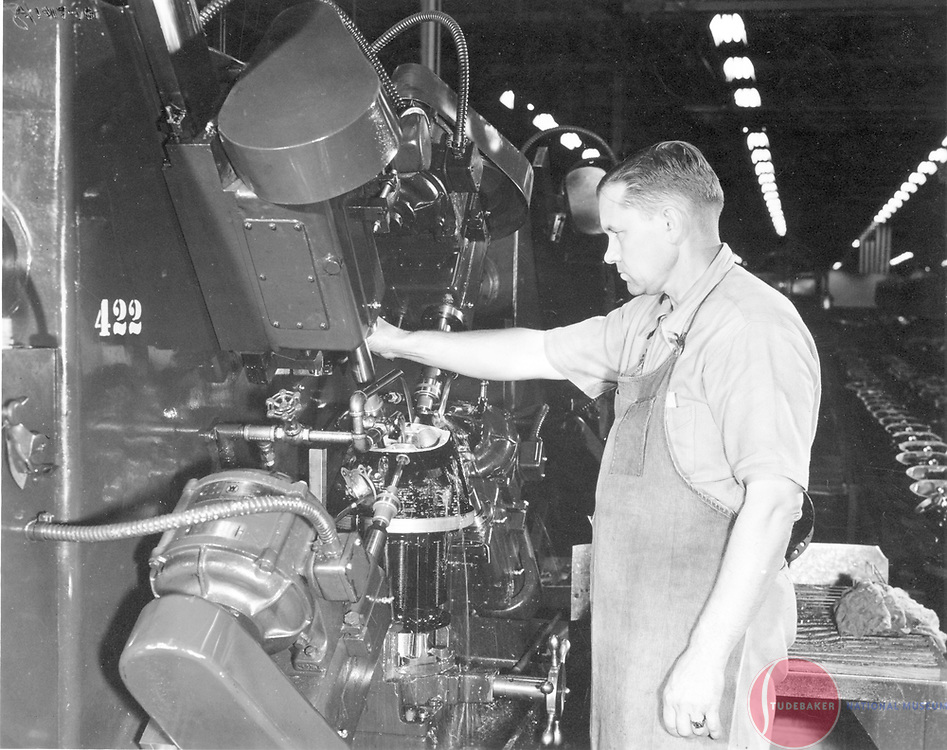 Finish reaming intake and exhaust valve guides and four rocker-arm bushings on cylinder head of a Studebaker-built Cyclone engine.  The operation is performed on a special four-spindle Snyder machine.