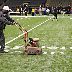 November 28, 2011; New Orleans, LA, USA; A worker removes a logo from the field prior to kickoff of a game between the New Orleans Saints and the New York Giants at the Mercedes-Benz Superdome. Mandatory Credit: Derick E. Hingle-US PRESSWIRE