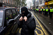 Student wearing balaclava marches against government education cuts in Regent Street. Holding a variety of splinter marches, students were campaigning against plans to raise tuition fees in England to up to £9,000 per year, with a vote expected in the House of Commons before Christmas. Police arrested 153 people during clashes in London on the third day of protests against plans to raise student tuition fees. The day ended with a stand-off with police in Trafalgar Square.
