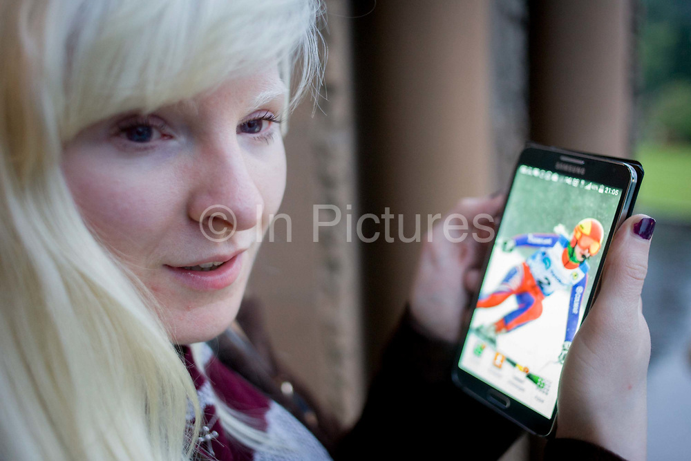 Partially-sighted skiing paralympian from the Sochi Olympics, Kelly Gallagher, Belfast, Northern Ireland. Having the sight of only a few feet and with poor close-up vision she uses her Smartphone that features a still of her downhill racing. From the chapter entitled 'The Law of Gravity' and from the book 'Risk Wise: Nine Everyday Adventures' by Polly Morland (Allianz, The School of Life, Profile Books, 2015).