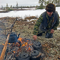 North of the Arctic Circle in Russia, Vasily Terentev prepares tea for his companions who rotate living on the land (without tents), while waiting for cows in the herd to calve.
