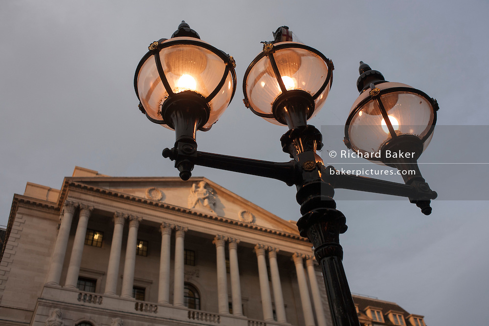 Early evening lighting illuminates the street, below the Bank of England, on 9th December 2016, in the City of London.