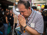 18 AUGUST 2015 - BANGKOK, THAILAND:  A man bows his head in prayer at a makeshift memorial in front of Erawan Shrine, which was damaged by a bomb Monday night. An explosion at Erawan Shrine, a popular tourist attraction and important religious shrine in the heart of the Bangkok shopping district, killed at least 20 people and injured more than 120 others, including foreign tourists, during the Monday evening rush hour. Twelve of the dead were killed at the scene. Thai police said an Improvised Explosive Device (IED) was detonated at 18.55. Police said the bomb was made of more than six pounds of explosives stuffed in a pipe and wrapped with white cloth. Its destructive radius was estimated at 100 meters.    PHOTO BY JACK KURTZ