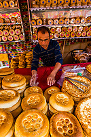 A merchant selling flatbread (nang) inhis shop in the International Grand Bazaar, Urumqi, Xinjiang Province, China.