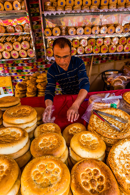 A merchant selling flatbread (nang) inhis shop in the International Grand Bazaar, Urumqi, Xinjiang Province, China.