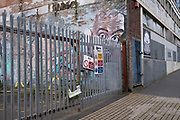 Street art graffiti of a face and pair of eyes looking over a fence in Digbeth on 14th March 2020 in Birmingham, United Kingdom. The eyes have a big brother feel of surveillance, as if people nearby are being watched.