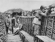 World War I 1914-1918: View inside the German trenches in France, 1915. Officers are examining plans while a rifleman stands keeping watch behind sandbags.  Military, Army, Soldier, Weapon, Smallarms