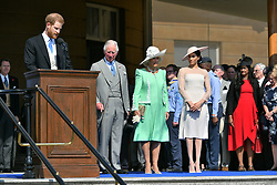 The Prince of Wales, the Duchess of Cornwall and the Duchess of Sussex, listen as the Duke of Sussex speaks during a garden party at Buckingham Palace in London, which the newly weds are attending as their first royal engagement as a married couple.