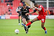 Barnsley defender Dimitri Cavare (12) powering past Walsall FC forward Corey Blackett-Taylor (38) during the EFL Sky Bet League 1 match between Walsall and Barnsley at the Banks's Stadium, Walsall, England on 23 March 2019.