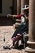 An elderly woman in traditional clothing hand spins alpaca wool under the columns of a stone arcade in Cusco, Peru.
