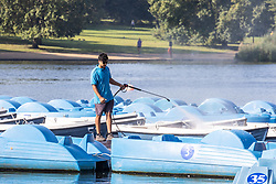 Licensed to London News Pictures. 16/09/2021. London, UK. A worker washes down the boats on the serpentine in Hyde Park, London as weather forcasters predict a warmer few days ahead with highs of 24c for London and the South East. Photo credit: Alex Lentati/LNP