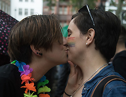 Portland Place, London, June 25th 2016. Thousands of LGBT people and their supporters gather for Pride in London, a colourful celebration of the hard-won rights of lesbian, gay, bisexual and transgender  people. PICTURED: Two women share a kiss in Soho Square.