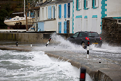 © Licensed to London News Pictures. 02/04/2018. St Austell, UK. A car drives through water on the road, caused by large waves at Portmellon, Cornwall. Cornwall experienced heavy rainfall overnight, causing rough seas, flooding and road closures across the county. Photo credit : Tom Nicholson/LNP