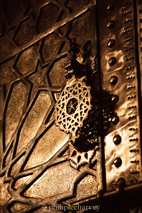 Brass door knocker on a decorated door to a house in the medina of Marrakech, Morocco