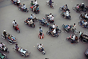 Phnom Penh, Cambodia. Traffic moves around a police officer directing traffic on Monivong Boulevard.