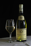 A bottle of Maison Louis Jadot Bourgogne Chardonnay 2002 white burgundy wine and a glass of white wine standing on a table top with a white cloth. Backlit backlight back light lit Black background, Maison Louis Jadot, Beaune Côte Cote d Or Bourgogne Burgundy Burgundian France French Europe European