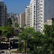 South America, Uruguay, Montevideo, sun-washed while buildings line a bisy residential street with a view to the national Capitol building.