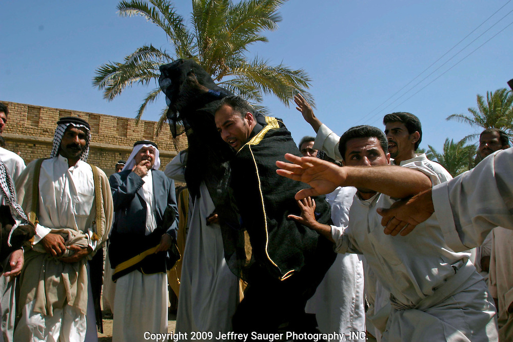 Emad Al-kasid, in gold and black, and his father Malik Al-kasid, in gray suit coat, participate in Hawaies, a traditional tribal Arabic dance, at the Al-kasid family's Istikbal, or homecoming, in their home village of Suq ash Shuyukh about 20 miles southeast of Nasiriyah, Iraq, Tuesday, July 29, 2003. ..When Malik Al-kasid's caravan approached, guns were fired to announce his family's arrival. The welcming party then, returns fire to welcome him. The two parties move toward each other dancing and shooting until they join in the middle where the Hawaies occurs. ..The Al-kasid family fled Iraq after the Gulf War and their part in the uprising against Saddam Hussein in 1991, spent 3 years in Rafa, Saudi Arabia and finally settled in Dearborn, MI. The family hasn't been home to Iraq in 13 years.