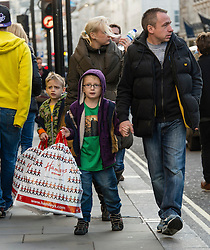 © Licensed to London News Pictures. 20/12/2014. London, UK. A family of Christmas shoppers on London's Regent Street on the last saturday before Christmas carry gifts bought from the toy shop Hamlets.  Photo credit : Richard Isaac/LNP