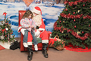 "Iowa USA, IA. Sioux City, Santa's house at the ""Festival of Trees"" ? A charity event in which people sell their self-decorated Christmas trees and the profits go to charity. Child sitting on Santa's lap, November 2006"