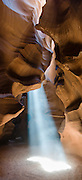 """A ray of sunlight pierces Upper Antelope Canyon, near Page, Arizona, USA. Antelope Canyon Navajo Tribal Park. Panorama stitched from three overlapping images. Published in """"Light Travel: Photography on the Go"""" book by Tom Dempsey 2009, 2010."""