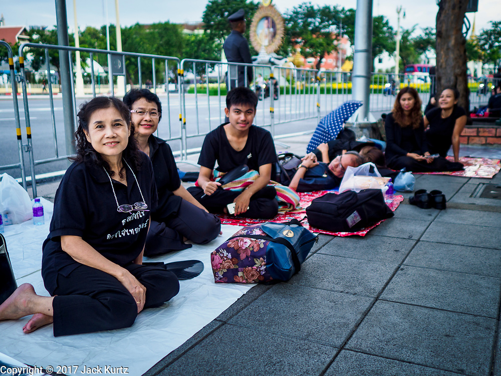 24 OCTOBER 2017 - BANGKOK, THAILAND: People camp on Ratchadadamnoen Rd near the entrance to the royal cremation site. People started camping out along Atsadang Road in Bangkok near the royal cremation site on Monday. The gates won't open until Wednesday morning and the cremation isn't until Thursday night, so most people will sleep outside, on sidewalks and footpaths for three nights. Hundreds of thousands of people are expected to try to get into Sanam Luang, the site of the cremation of Bhumibol Adulyadej, the Late King of Thailand, but the site will only hold about 60,000 people. The Thai government has built replica crematoriums around Bangkok to accommodate the overflow crowds.        PHOTO BY JACK KURTZ