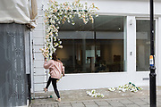 A lady descends a ladder while installing a floral design to the exterior of a West End business, on 4th March 2019, in London England.