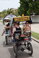 Taking a pedicab on the streets of Cienfuegos, Cuba.