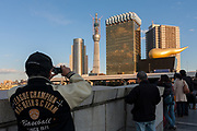 A tourist takes a photo of the Tokyo Skytree under construction seen behind the  buildings of the Asahi Breweries Headquarters in Asakusa, Tokyo, Japan. Wednesday, December 29th 2010 When finished this telecommunications tower will measure 634 metres from top to bottom making it the tallest structure in East Asia..