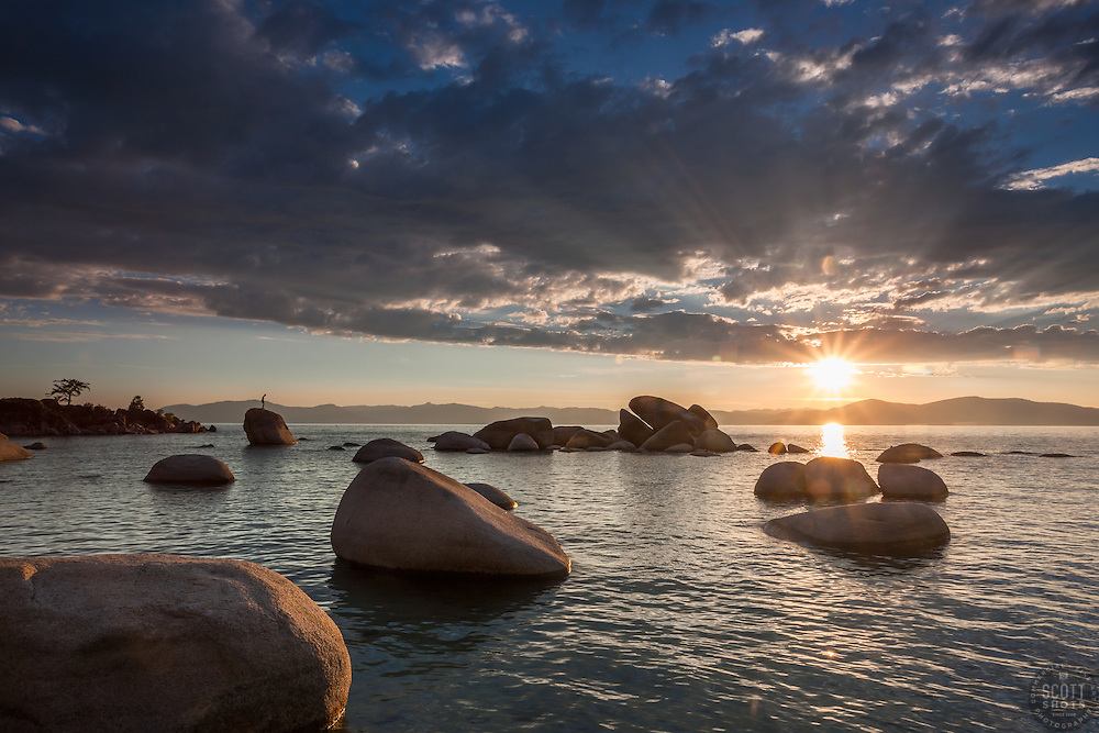 """""""Sunset at Whale Beach, Tahoe 2"""" - Photograph of a sunset at Whale Beach on the East Shore of Lake Tahoe. A man standing on a rock and Whale Rock can be seen in the distance."""