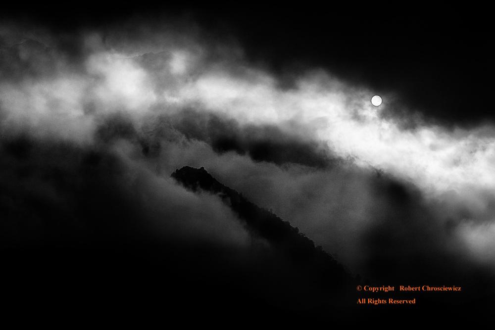 Ring of Light (B&W): Light of an early sunset radiates through a heavy fog and round a volcanic peak, Sapa Vietnam.