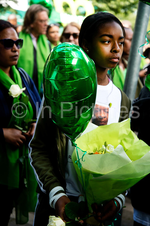 Commemoration of the first anniversary of the devastating fire of 14th/15th June  2017 in Grenfell Tower, Lancaster West Estate, West London, United Kingdom when 72 people were killed. After a 72 second silence one second for each victim survivors and family members held a silent walk to the tower. A young girl holds a green balloon and flowers.