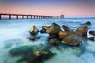 Bridge in the sea at sunset