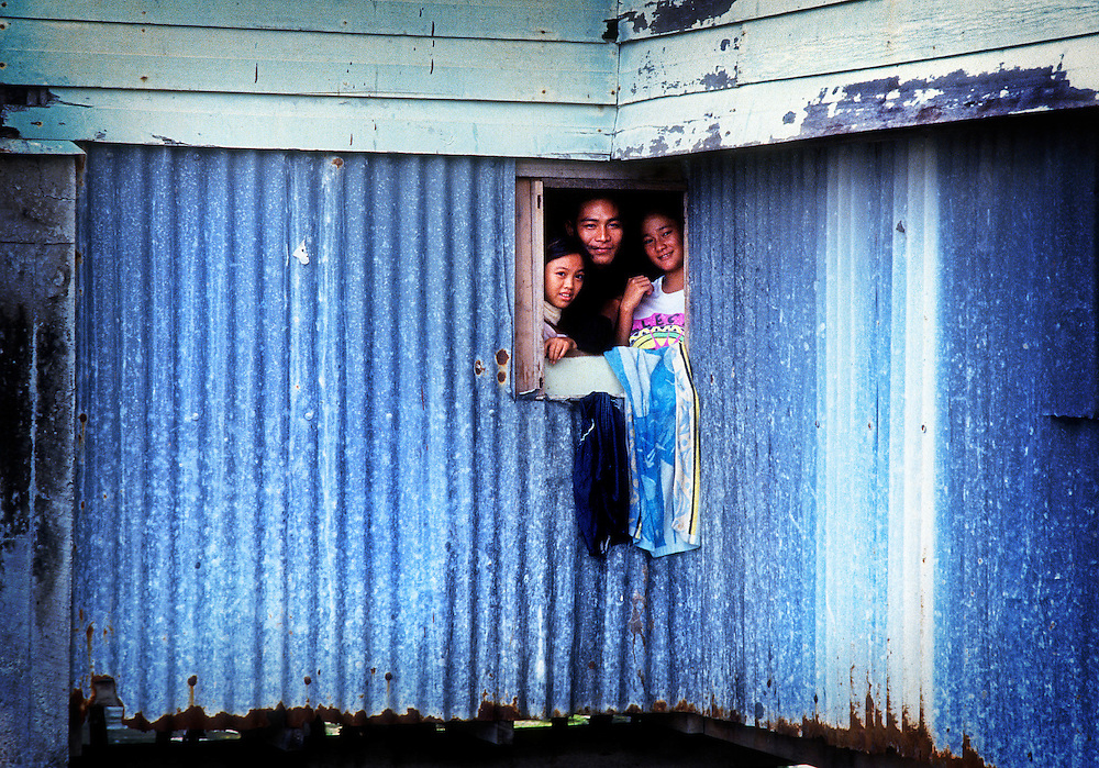 Family looking out from river house on stilts, Borneo<br /> Client Raleigh International