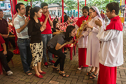 April 14, 2017 - Medan, North Sumatra, Indonesia - Indonesian Catholic women kiss the feet of the statue of Jesus Christ during the Good Friday in the church of Santa Maria Katedral in Medan on April 14, 2017, Indonesia. As Christians mark Friday as the death, of the life after the third day, otherwise known holy week of Easter Sunday in celebration of the crucifixion and resurrection Jesus Christ, a as Muslim-dominated population country. Christians in Indonesia visited the grave of their families member  who believe in living with Jesus Christ. (Credit Image: © Ivan Damanik via ZUMA Wire)