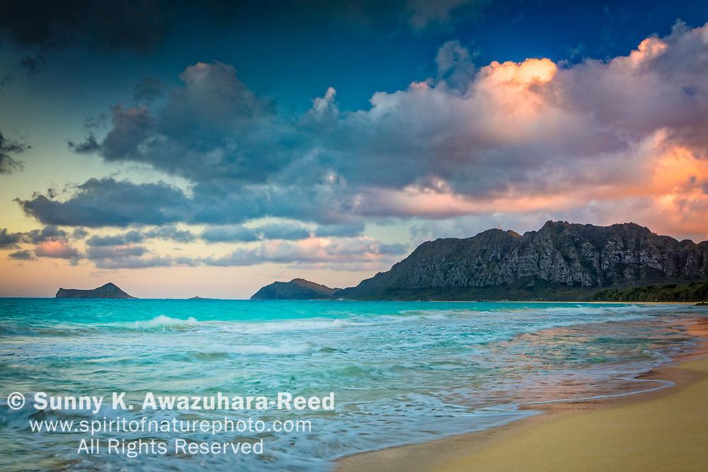 Sunset clouds over Rabbit Island and Koʻolau Range, Bellows Beach, Oahu Island, Hawaii.