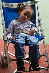 Child with brain damage sleeping in a pushchair,