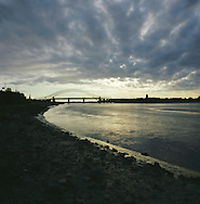 The sun setting behind the Silver Jubilee road bridge in Runcorn which crosses the river Mersey to Widnes. The Mersey is a river in north west England which stretches for 70 miles (112 km) from Stockport, Greater Manchester, ending at Liverpool Bay, Merseyside. For centuries, it formed part of the ancient county divide between Lancashire and Cheshire.