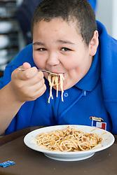Secondary School student eating spaghetti Bolognese in the Restaurant,