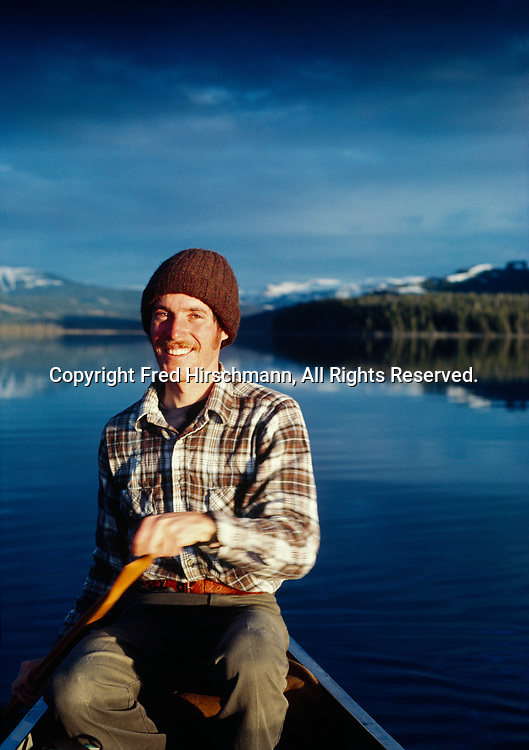 Fred Hirschmann canoeing on the Southeast Arm of Yellowstone Lake, Absaroke Mountains beyond, Yellowstone National Park, Wyoming.