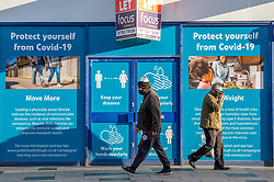 © Licensed to London News Pictures. 23/10/2020. Slough, UK. Two men pass each other as they walk past an empty shop with coronavirus safety advice covering the windows. Slough will move to Local COVID Alert Level: High (Tier 2) at 00:01 BST on Saturday 24th October 2020 after an increase in people infected with the COVID-19 coronavirus. Photo credit: Peter Manning/LNP