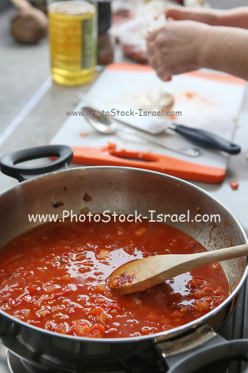 Cooking Moroccan meatballs in tomato sauce. The sauce simmering in a pot