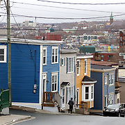 A man walks by houses on Signal Hill Road referred to as jellybean houses in St. John's, Newfoundland and Labrador, Canada, on Monday, June 3, 2019. The homes, which have a varying colors from house to house, are a common sight in St. John's.  THE BLADE/KURT STEISS <br /> MAG NewfoundlandXX